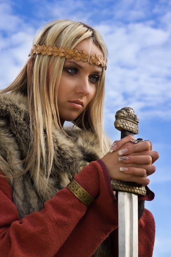 Guerrero de la muchacha de Vikingo en un fondo del cielo azul foto de archivo