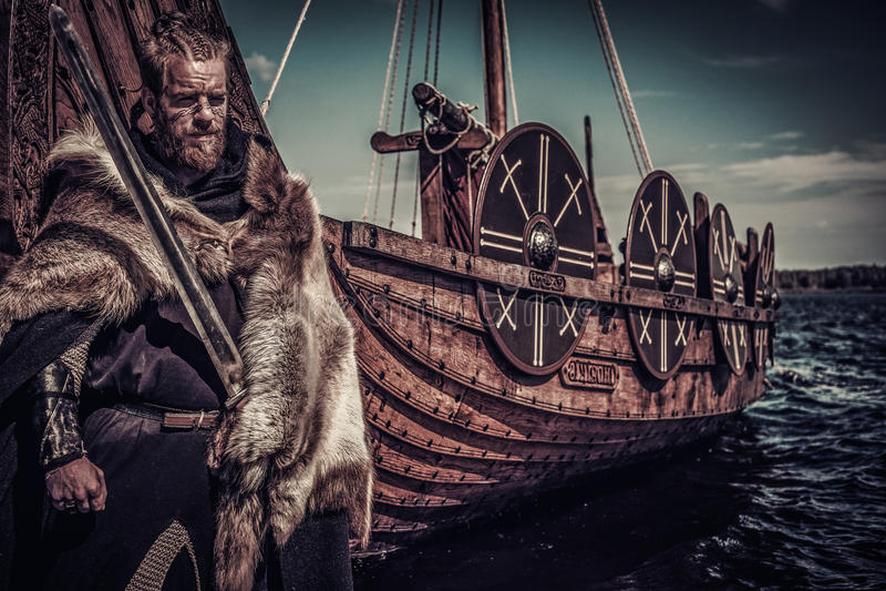 Guerrero de Viking con la espada que se coloca cerca de Drakkar en la costa imágenes de archivo libres de regalías