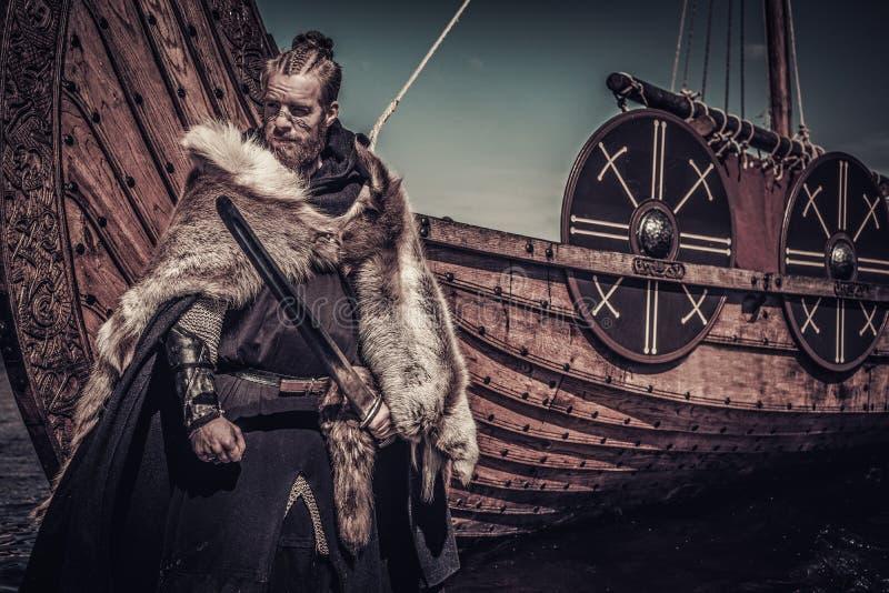 Guerrero de Viking con la espada que se coloca cerca de Drakkar en la costa imagenes de archivo