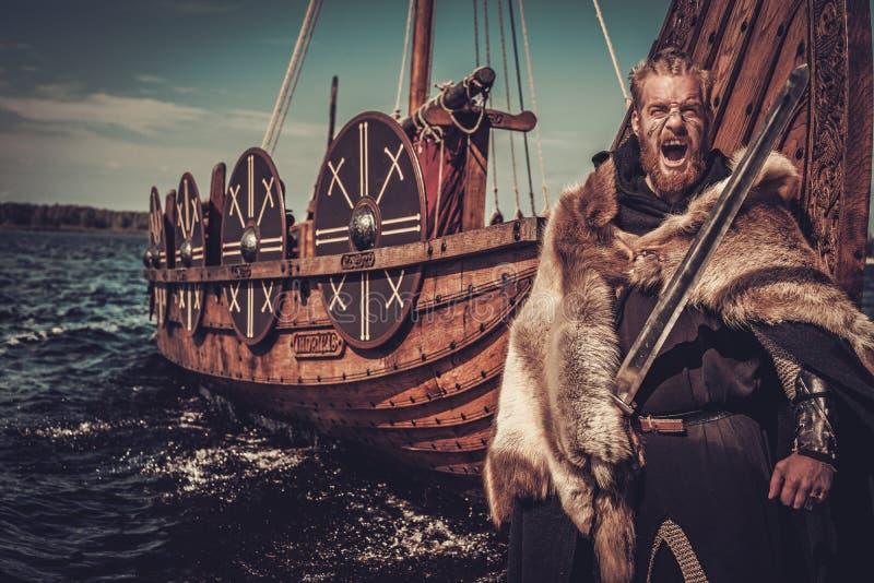 Guerrero de Viking con la espada y el escudo que se colocan cerca de Drakkar en la costa fotografía de archivo libre de regalías