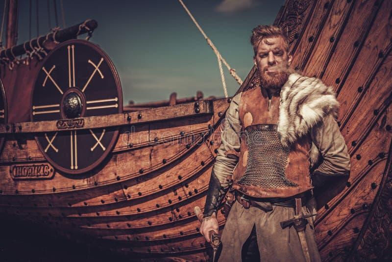 Guerrero de Viking con las hachas que se colocan cerca de Drakkar en la costa imagen de archivo