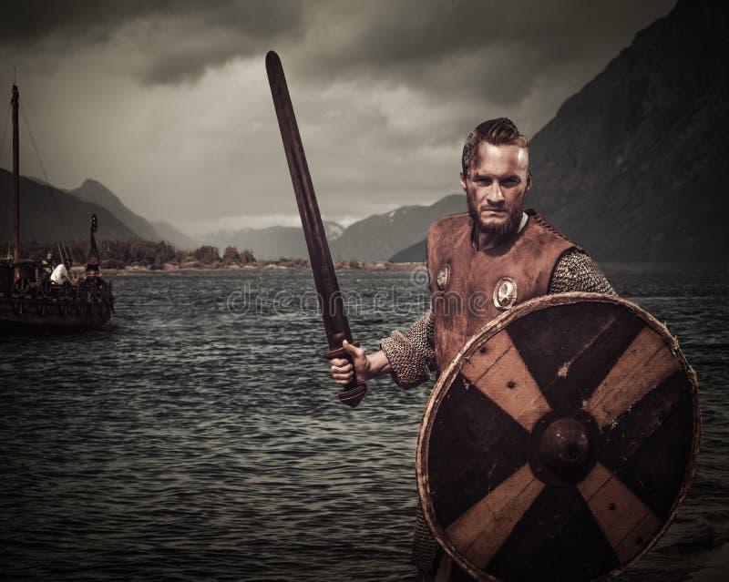Guerrero de Viking en el ataque, colocándose a lo largo de la orilla con Drakkar y de las montañas en el fondo imagen de archivo libre de regalías