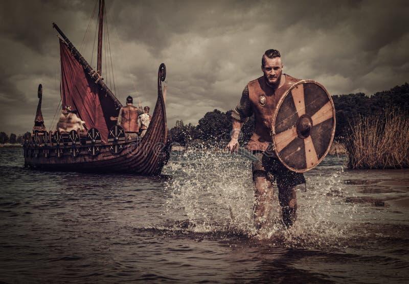 Guerrero de Viking en el ataque, corriendo a lo largo de la orilla con Drakkar en el fondo imagenes de archivo
