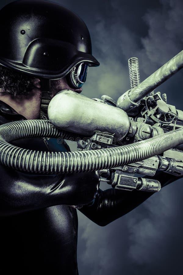 Guerrero del futuro con la escopeta enorme del cañón del laser sobre s azul imágenes de archivo libres de regalías