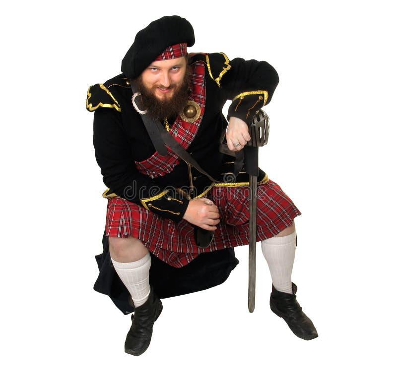 Guerrero escocés con la botella de vino rojo fotografía de archivo