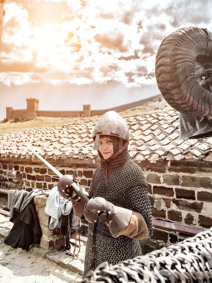 Guerrero medieval del muchacho, muchacho en la armadura del caballero medieval en correo en cadena, un casco, armadura, sostenien foto de archivo