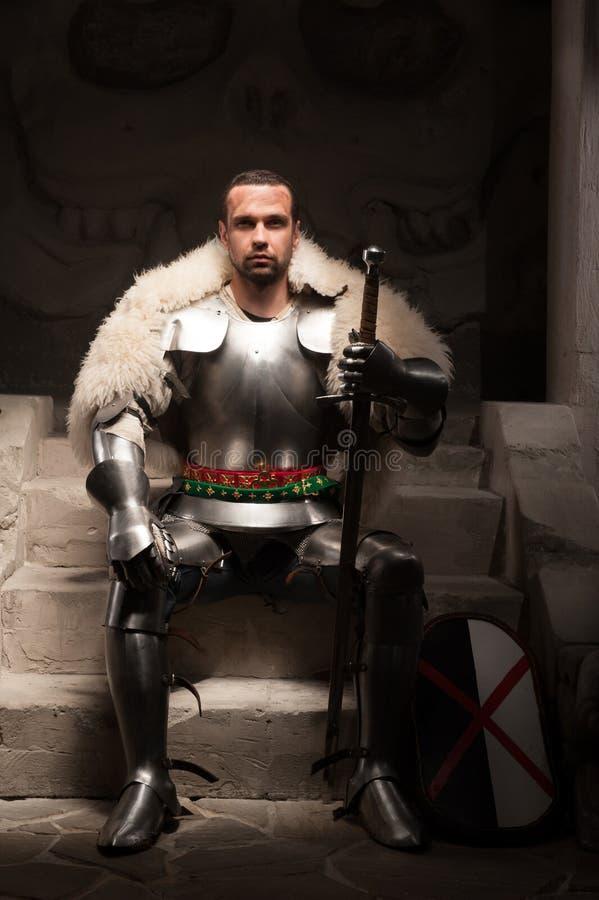 Guerrero medieval en capa de la armadura y de la piel imagenes de archivo
