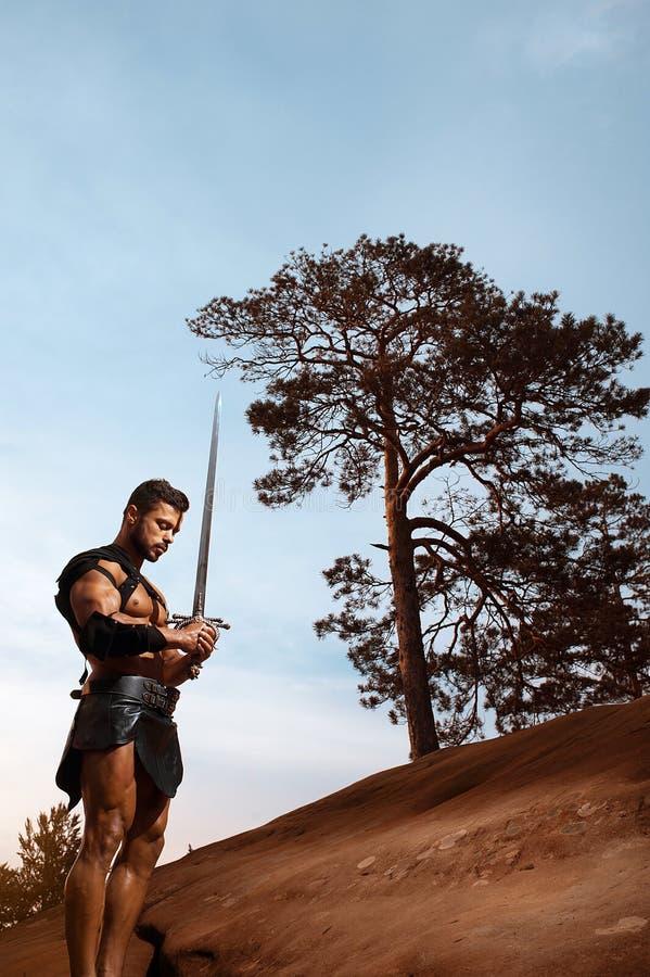 Guerrero muscular joven con una espada en las montañas imagen de archivo libre de regalías