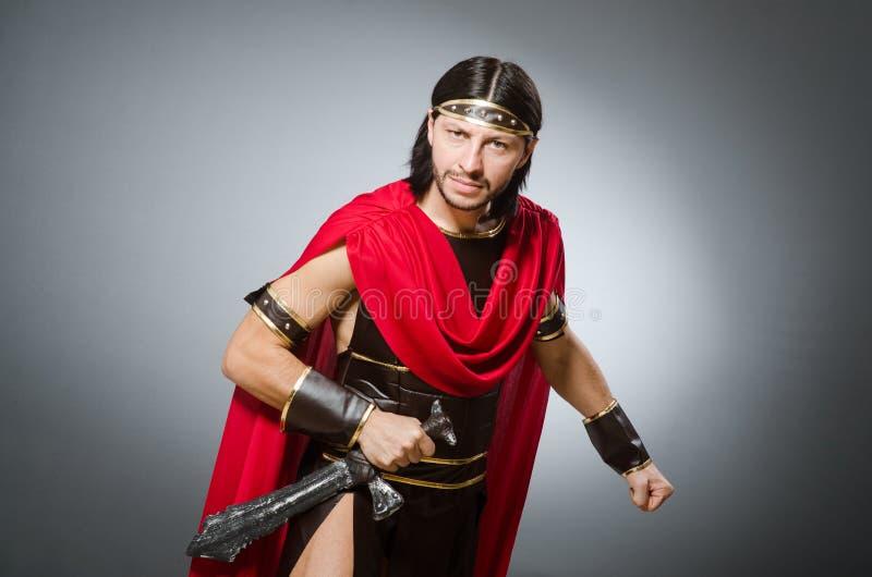 Guerrero romano con la espada contra fondo foto de archivo