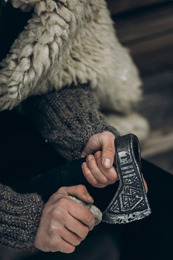 Guerrero septentrional con el arma, vikingo que afila su hacha antes de b fotos de archivo libres de regalías