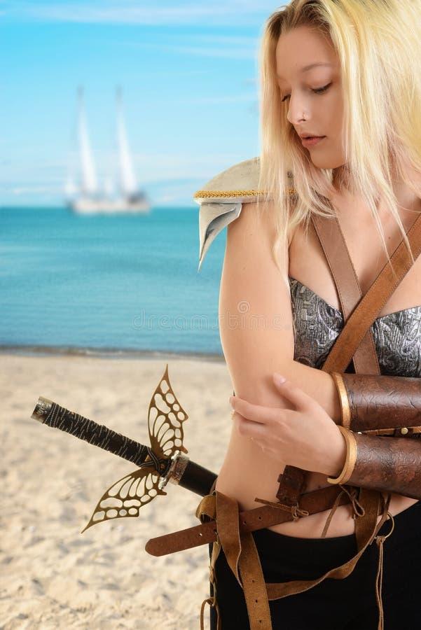 Guerrière de femme à la plage avec le bateau à l'arrière-plan image libre de droits