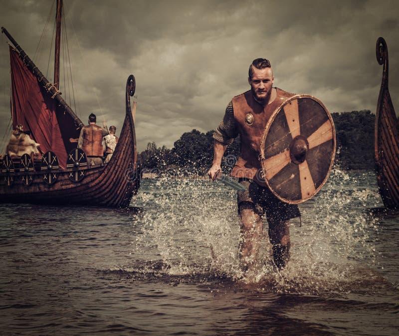 Guerrier de Viking dans l'attaque, fonctionnant le long du rivage avec Drakkar sur le fond image stock