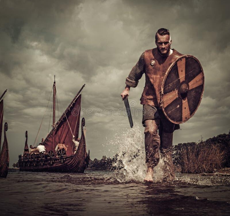 Guerrier de Viking dans l'attaque, fonctionnant le long du rivage avec Drakkar sur le fond photo libre de droits