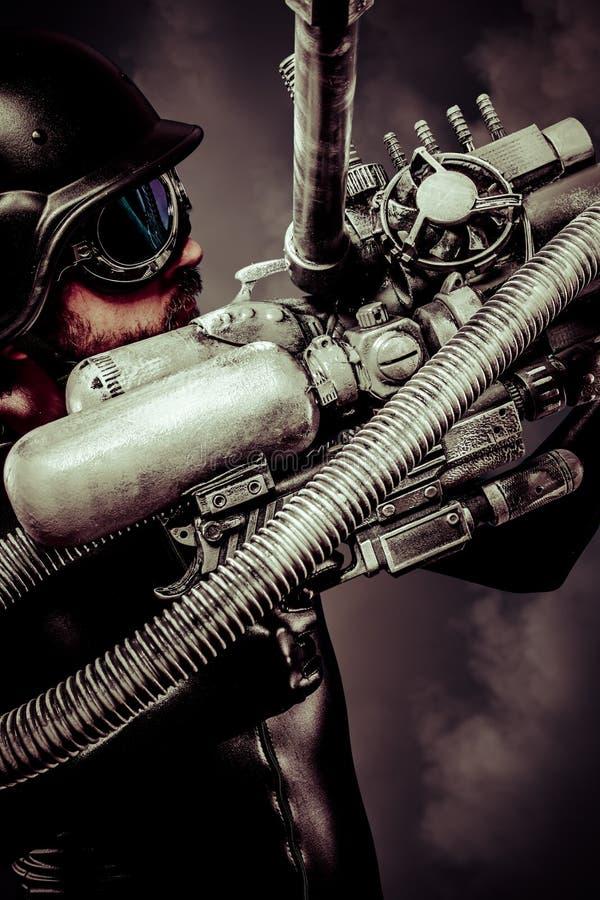 Guerriero del futuro con il fucile da caccia enorme del cannone del laser sopra caos immagini stock