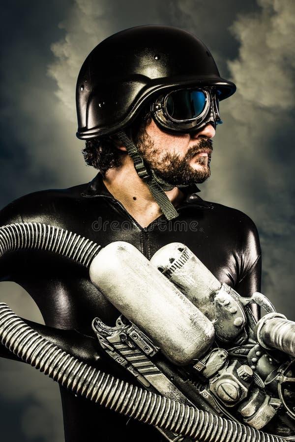 Guerriero del futuro con il fucile da caccia enorme del cannone del laser sopra le nuvole fotografia stock