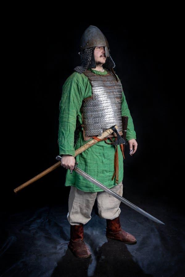Guerriero di età di vichingo dello slavo in armatura e casco con la spada e l'ascia fotografia stock