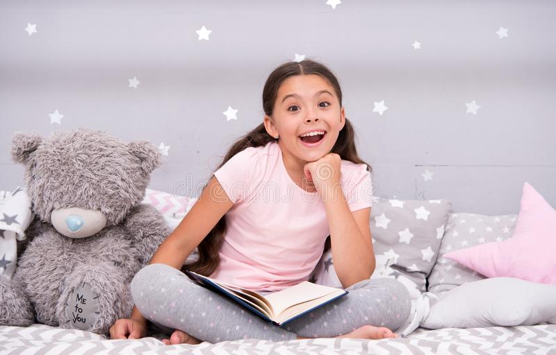 Guess her favorite fairy tale. Girl child sit bed with teddy bear read book. Kid prepare to go to bed. Pleasant time in stock images