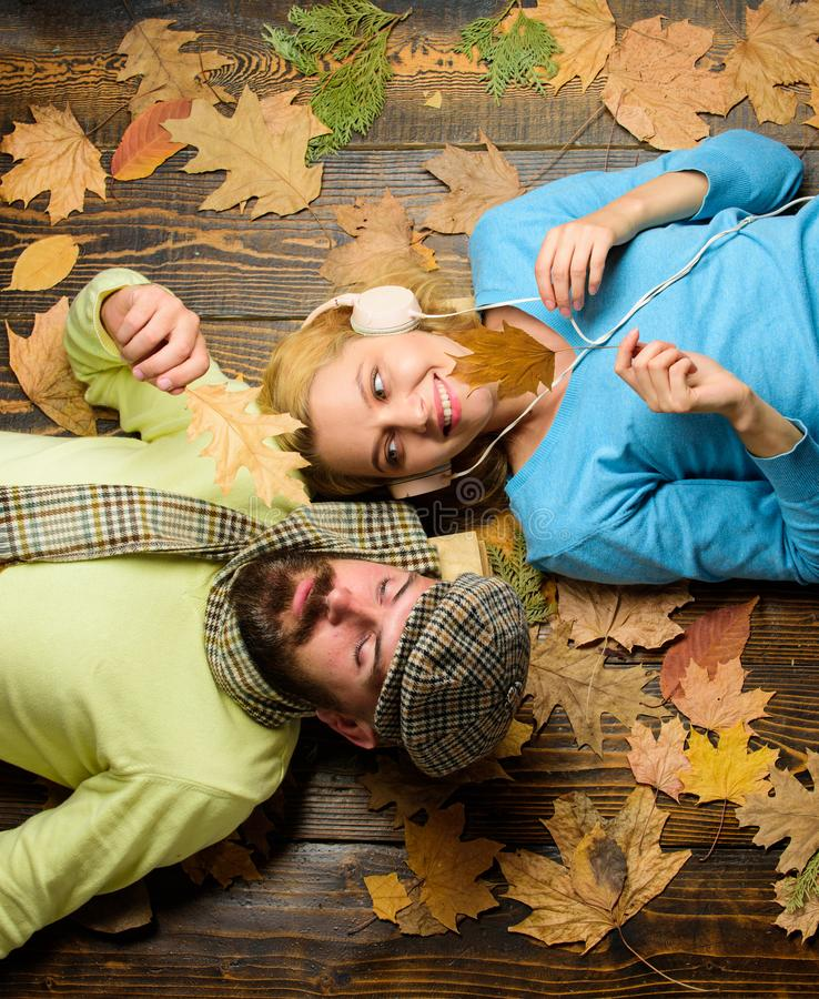 Guess her favorite song. Fall date pleasant cozy atmosphere. Man bearded dreamy face and lady listening music headphones. Lay on wooden background top view stock images