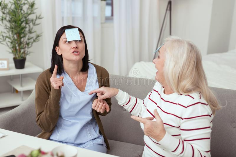 Optimistic elder woman and caregiver having fun. Guess who. Jolly elder women and caregiver communicating while playing game stock images