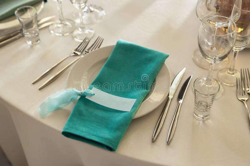 Guest Card and Aquamarine Serviette with lying on the dinner plate.  stock photos