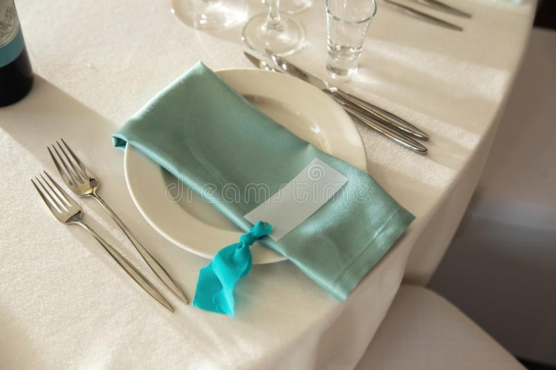 Guest Card and Aquamarine Serviette with lying on the dinner plate.  stock images