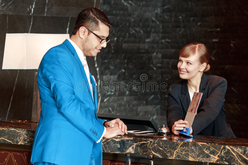 Guest communicating with a receptionist. Do you have a spa. Good-looking businessman leaning against the hotel counter and viewing information holder which is royalty free stock photo