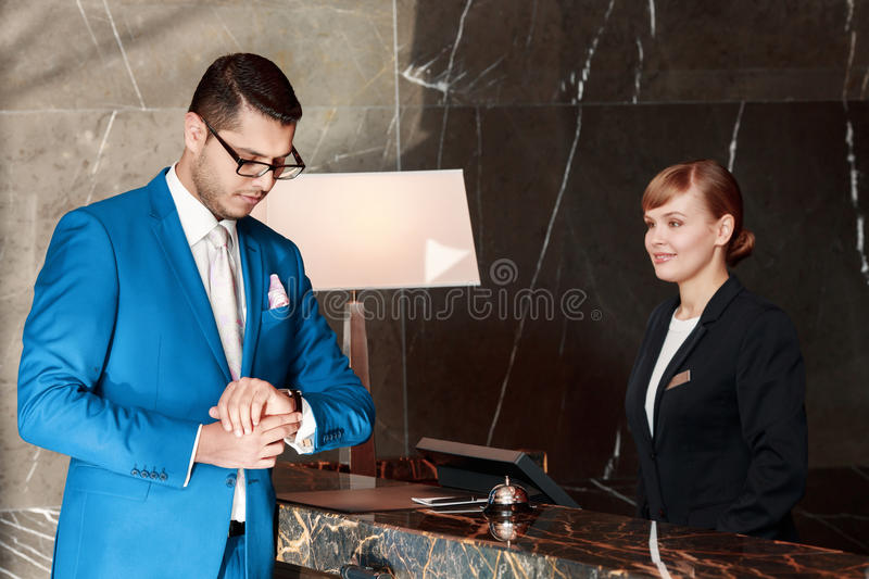 Guest communicating with a receptionist. Time is money. Businessman in blue suit looks at his watch standing just in front of the reception desk with smiling royalty free stock photo