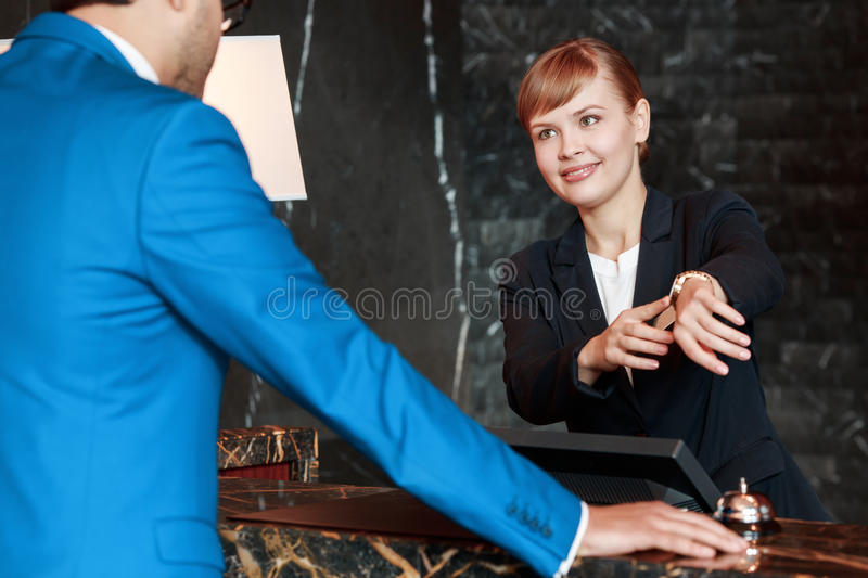 Guest communicating with a receptionist. What is local time. Selective focus of an attractive hotel receptionist pointing to her watch and showing local time to stock photo