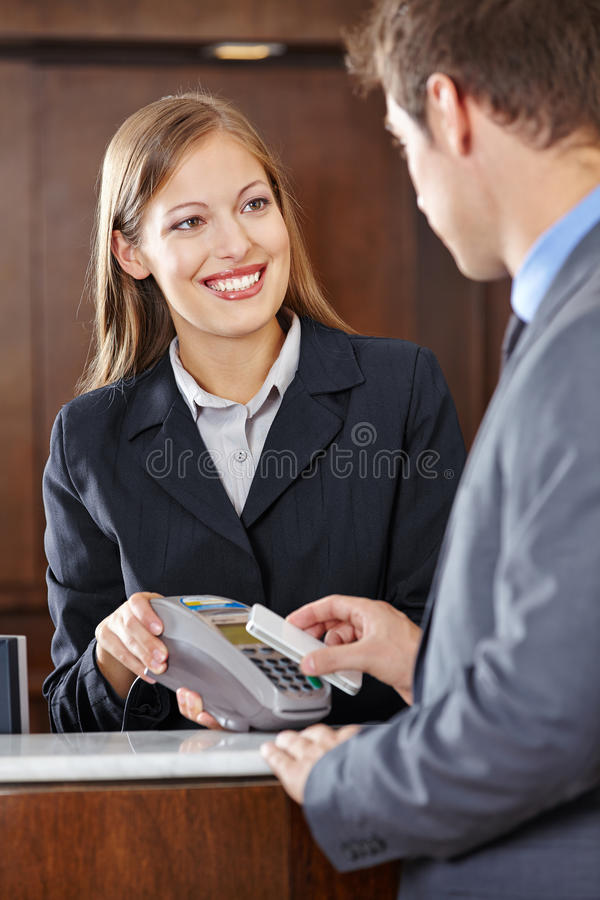 Guest in hotel paying bill with smartphone via NFC royalty free stock photo