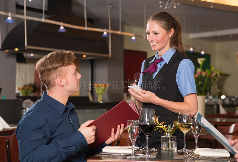 Guest in a restaurant orders meal from menu royalty free stock photo