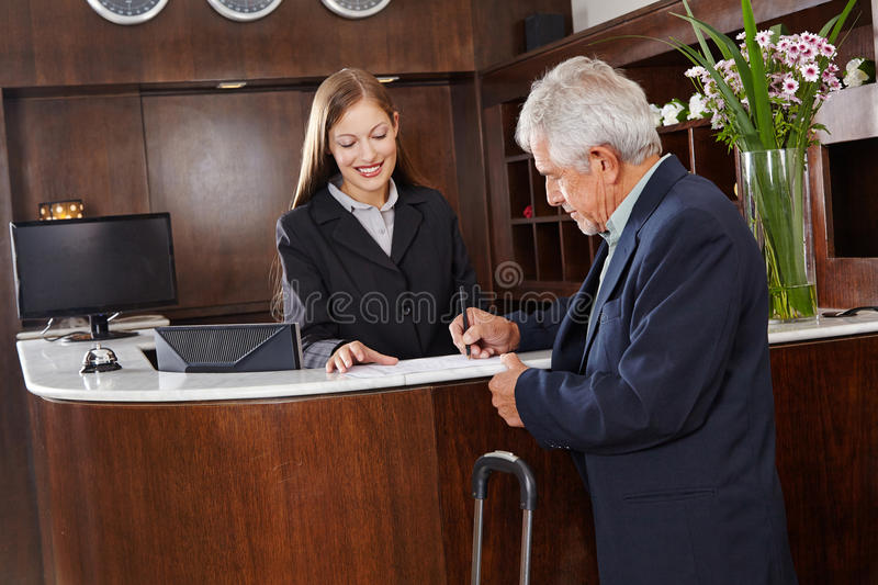 Guest signing form at hotel reception royalty free stock photo