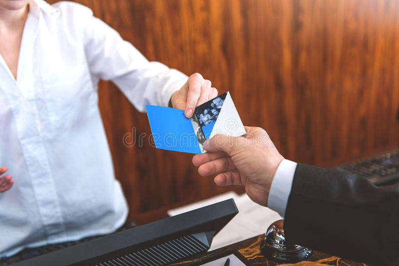 Guest taking room key card at check-in desk stock image