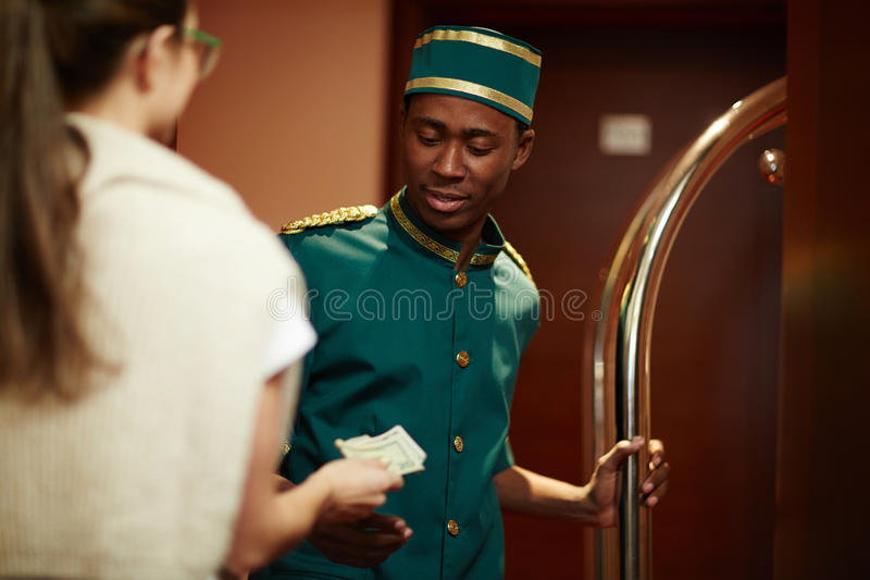 Guest Tipping Hotel Staff. Portrait of smiling young African boy working as bellhop in luxury hotel, getting tip from women guest for delivering luggage to room royalty free stock photos