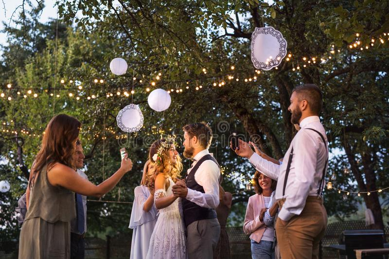 Guests with smartphones taking photo of bride and groom at wedding reception outside. royalty free stock image