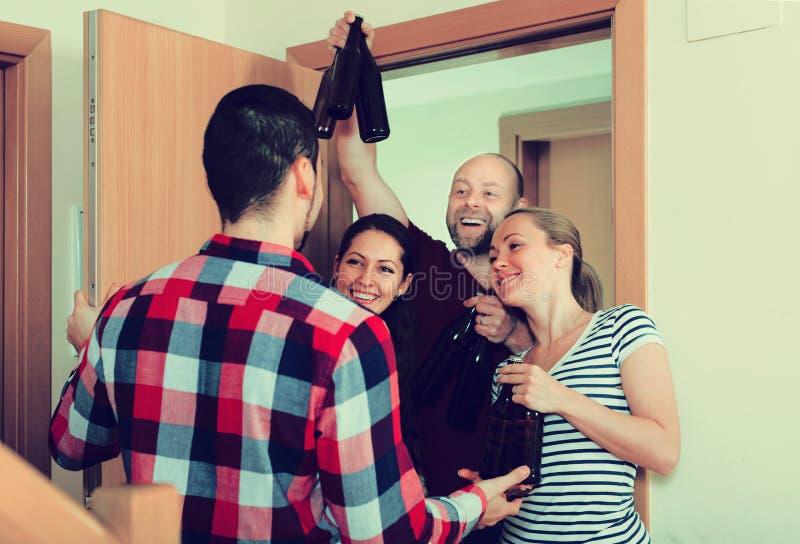 Guests standing in doorway. Happy russian guests with bottles standing in doorway and smiling stock photo