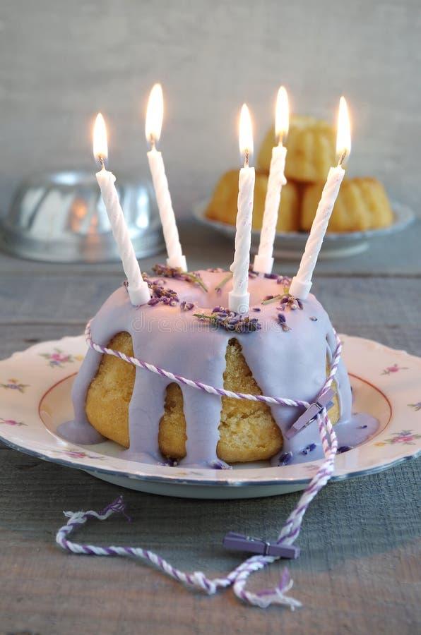 Gugelhupf med isläggning och lavendel som födelsedagkakan arkivbilder