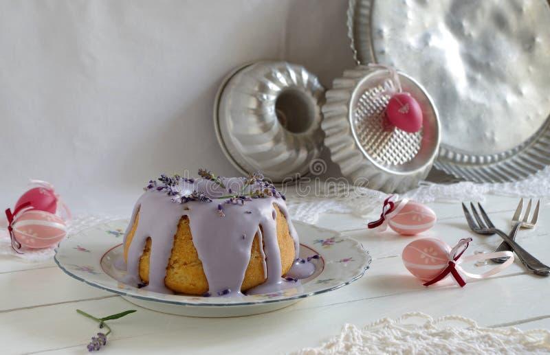 Gugelhupf met lilac suikerglazuur en lavendel aan Pasen stock afbeeldingen