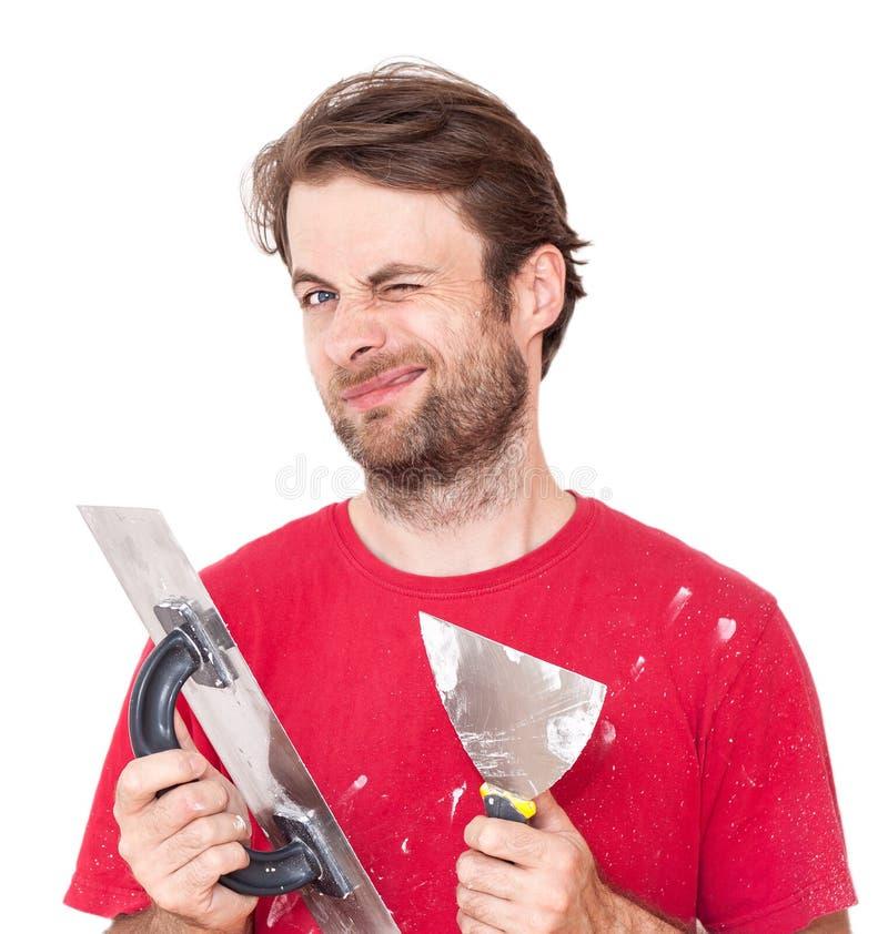 Guiñando al trabajador manual con la pared que enyesa las herramientas aisladas en blanco foto de archivo