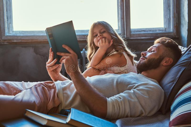 Guión joven hermoso de la lectura del padre su pequeña hija en cama fotos de archivo