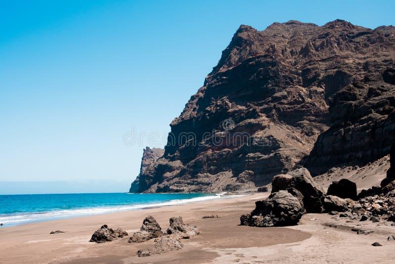 gui gui海滩风景看法在gran卡纳里亚海岛在有壮观的山的西班牙环境美化和清楚的天空蔚蓝和含沙 免版税库存图片
