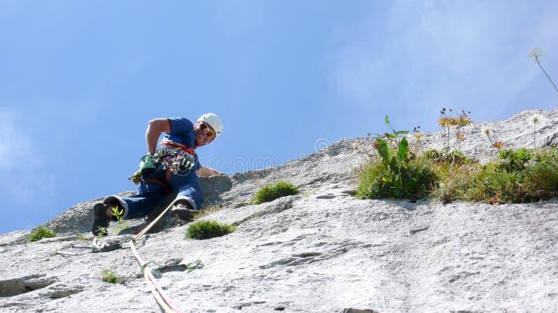 Guia da montanha que escala um passo íngreme da laje de uma rota da escalada de hard rock nos cumes de Suíça fotos de stock royalty free