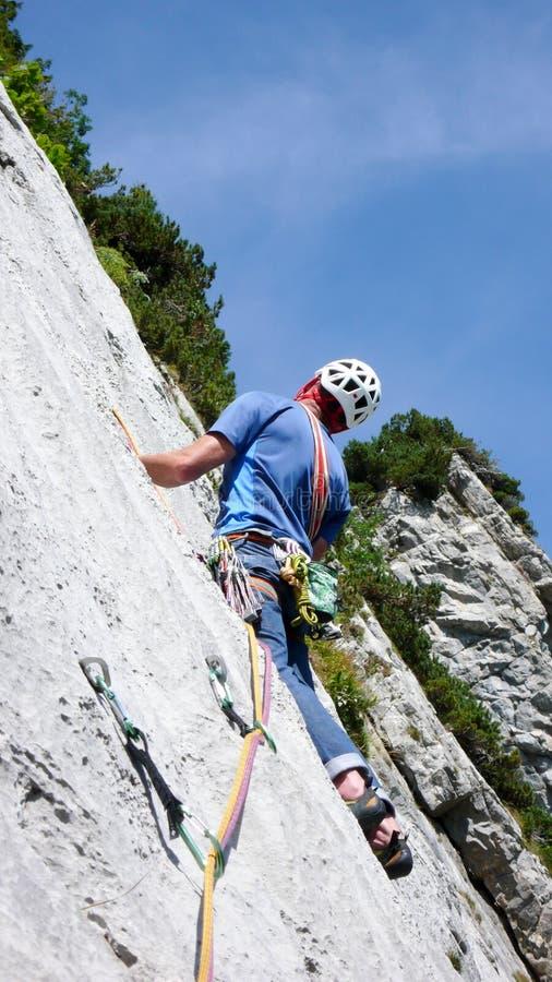Guia da montanha que escala um passo íngreme da laje de uma rota da escalada de hard rock nos cumes de Suíça foto de stock royalty free