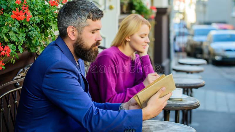Guia a datar Povos da reunião com interesses similares O homem e a mulher sentam o terraço do café A menina interessou que ele le imagem de stock