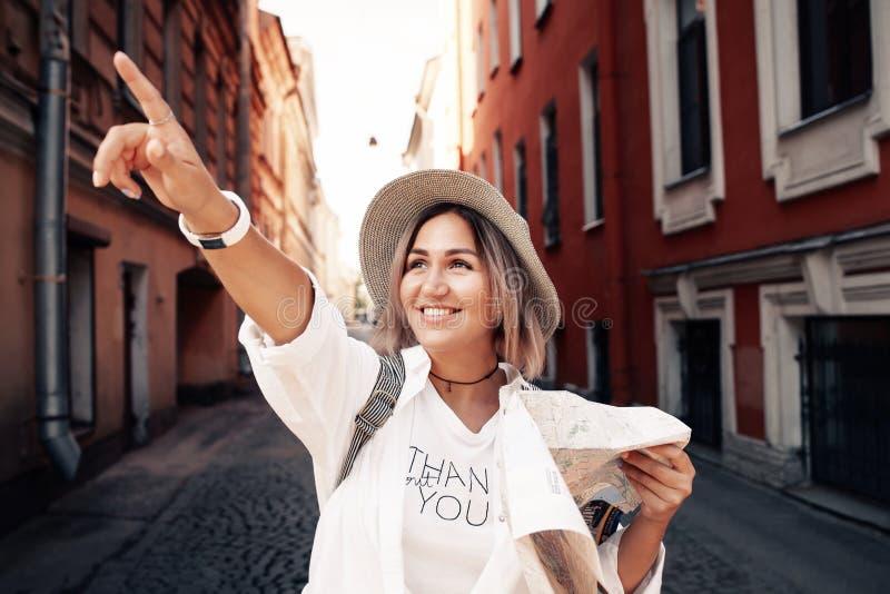 Guia do curso Viajante fêmea novo com trouxa e com o mapa na rua conceito do curso fotos de stock royalty free