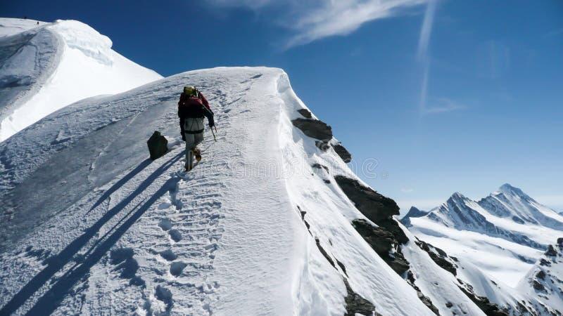 Guia e cliente da montanha em um título norte íngreme da inclinação da cara para a cimeira com uma grande ideia do lan circunvizi imagens de stock