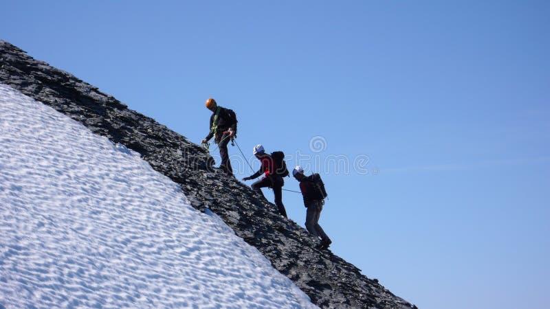 Guia masculino da montanha que dirige a um pico alto com dois clientes em um dia bonito imagens de stock royalty free