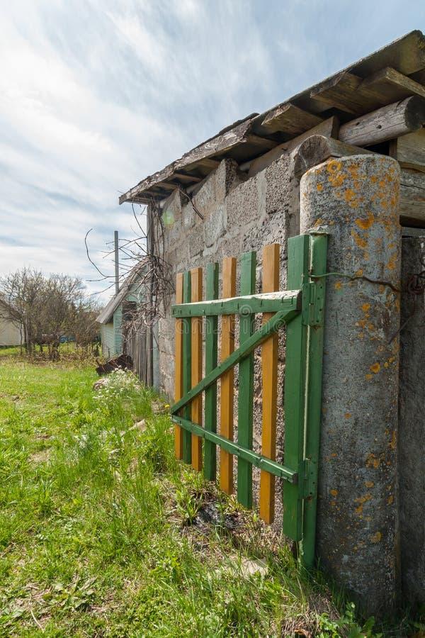 guichet en bois rural sur un pilier concret sur le fond d'une grange et d'un ciel bleu nuageux photos libres de droits