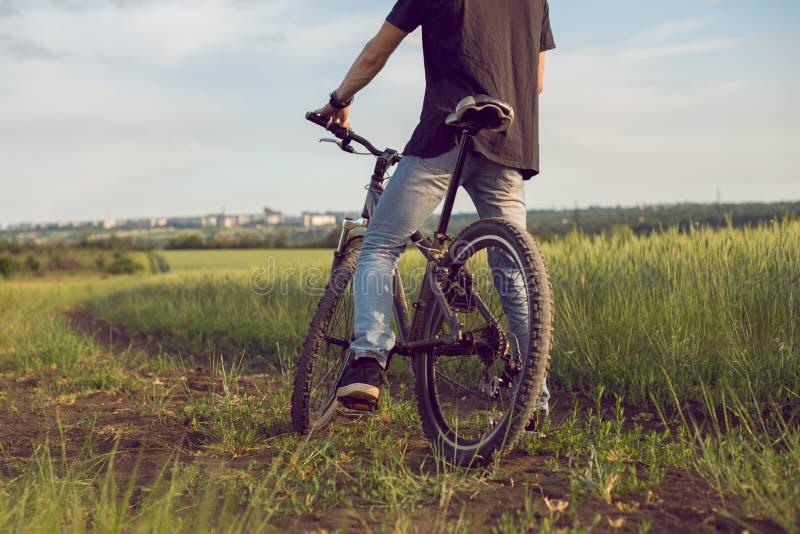 Guida campestre del giovane ciclista, ciclare, attività e sport Trasporto rispettoso dell'ambiente, aria pulita, attività, healt fotografia stock