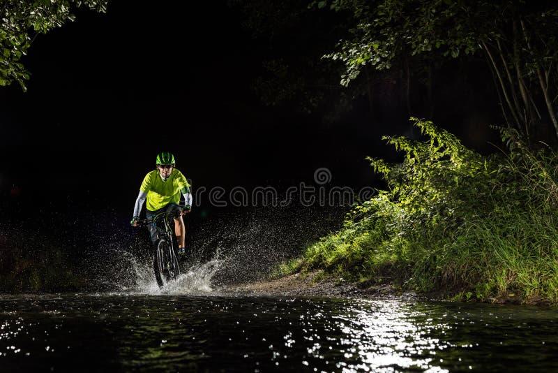Guida del ciclista in mountain-bike nella corrente della foresta fotografie stock libere da diritti