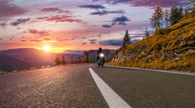 Guida del driver di motociclo in strada principale alpina Fotografia all'aperto, fotografia stock